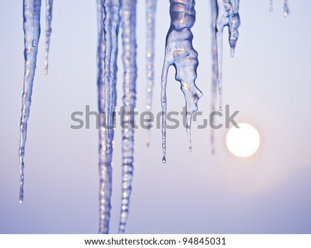 Thawing icicles isolated on blue with sun in background / face ice / - stock photo