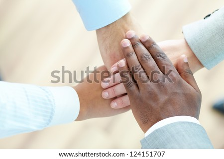 The above view of a business team piling hands as a sign of companionship - stock photo
