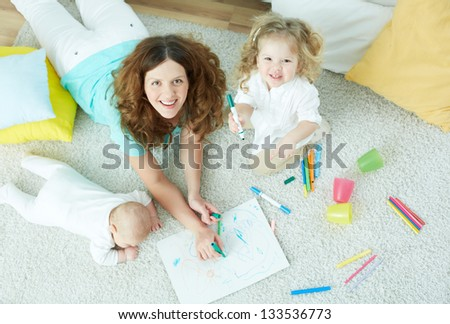 The above-view portrait of a beautiful babysitter looking after cute kids - stock photo