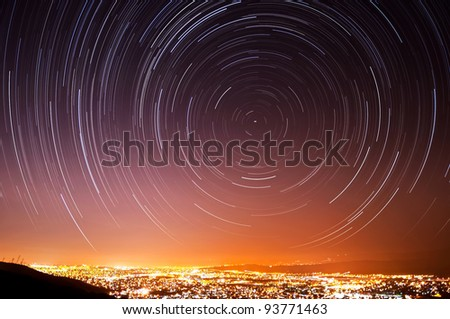 The accumulated star trails in the night sky above San Jose, California. - stock photo