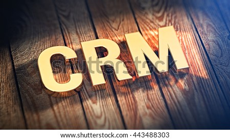 """The acronym """"CRM"""" is lined with gold letters on wooden planks. 3D illustration image - stock photo"""