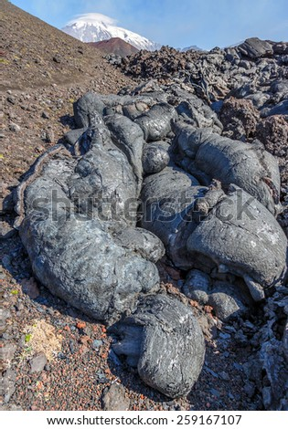 The active lava flow from a new crater on the slopes of volcanoes Tolbachic. Volcano Tolbachic Sharp on background - Kamchatka, Russia - stock photo