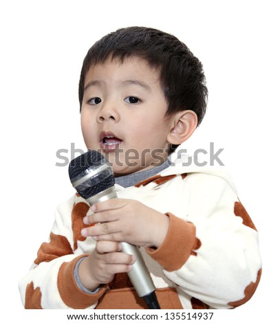 The adorable 3-year-old boy love singing, having a concert. - stock photo