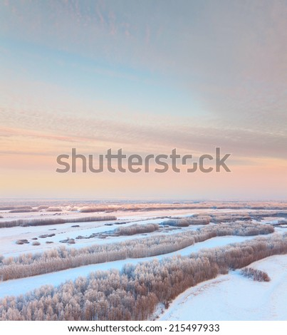 The Aerial view of forest in hoarfrost on wooded terrain in time of winter frosty morning. Thin clouds are painted by a bright rays of rising sun. - stock photo