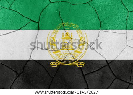 The Afghanistan flag painted on a cracked desert ground surface - stock photo