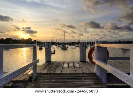 The afternoon golden sun sets over Iron Cove , views from the timber wharf  lead the eye through to moored boated bobbing on the waters from Liechhardt Park, NSW, Australia. - stock photo