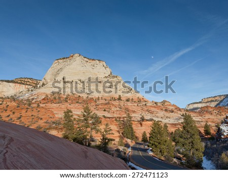 The afternoon sunshine lighting up a large mountain formation and the rising moon in Zion National Park, Utah. - stock photo