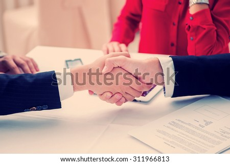 The agreement was signed. Three successful and confident businesspeople shake hands. Businesspeople in formal attire sitting in an office at a desk close-up view of hands - stock photo