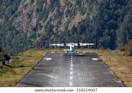 The aircraft takes off on the runway of the Tenzing-Hillary airport Lukla - Nepal, Himalayas - stock photo
