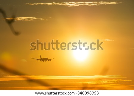 The airplane landing flying through the sun. - stock photo