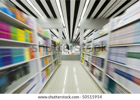 The aisles in a public library with shelves full of books - stock photo