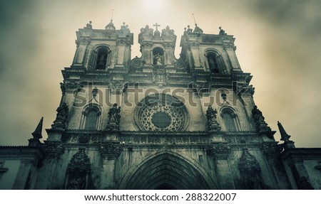The Alcobaca Monastery in gloomy cloudy day. Medieval Roman Catholic Monastery in Alcobaca (Portugal) is UNESCO World Heritage Site. Sun light rays through the clouds. Retro aged toned photo. - stock photo