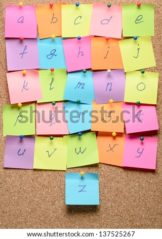 The alphabet with stickers note pinned on a cork bulletin board - stock photo