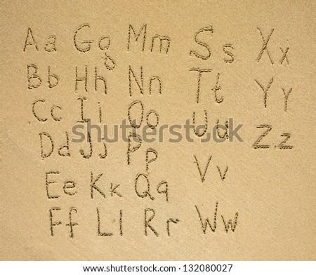 The alphabet written on a sand beach. - stock photo