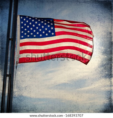 The American Flag Flapping Against A Blue Sky On A Flag Pole. Vintage background - stock photo