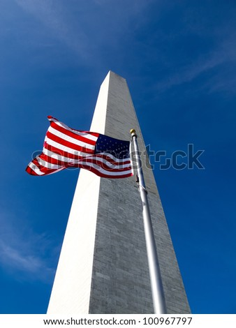 The American Flag waves with the Washington Monument in the background - stock photo