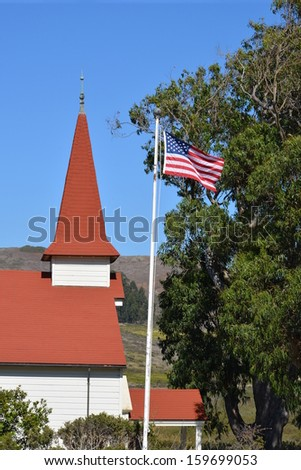 The American flag waving in front of an old building - stock photo