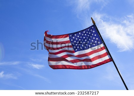 the American national flag in the wind against a blue sky in summer - stock photo