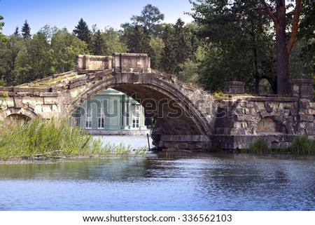 The ancient destroyed bridge in park and pavilion of Venus (1793) is visible under a bridge arch. Gatchina, St. Petersburg, Russia - stock photo
