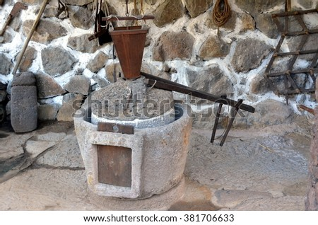 the ancient part of the oil press millstone ancient olive oil production machinery, stone mill and mechanical press is found in close up in a rustic farm. - stock photo