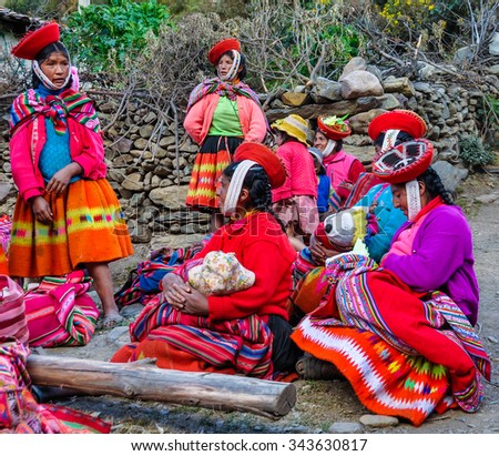 THE ANDES, PERU - MAY 30, 2012: Quechua women with children in a village in the mountains of The Andes over Ollantaytambo, Peru - stock photo
