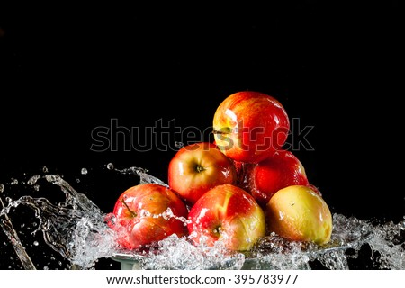 The apples lying on the silver side and flying water on a black background - stock photo
