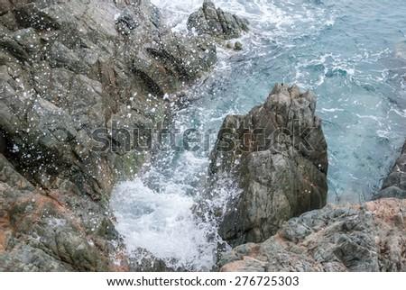 The aqua waters of the Caribbean splashing against a rocky coast - stock photo