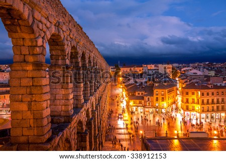 The aqueduct of Segovia, Spain, was built during the roman empire and stands as it was conceived until today. The aqueduct is built of brick-like granite blocks perfectly carved. - stock photo