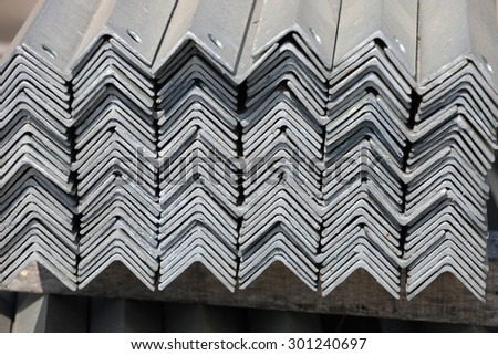 The arrangement of galvanized steel angles bunch in warehouse. - stock photo