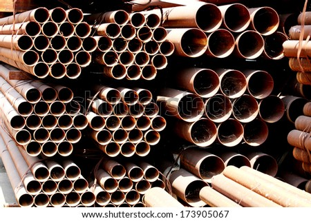 The arrangement of rust steel pipes in warehouse. - stock photo