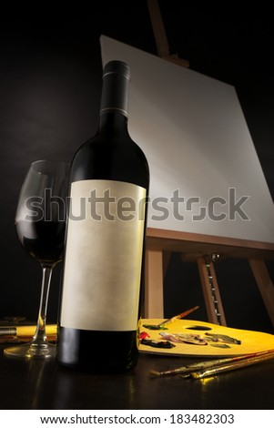 The art of wine depicted with a excellent bottle of wine, a glass and some artist materials, with a blank canvas in the background. - stock photo