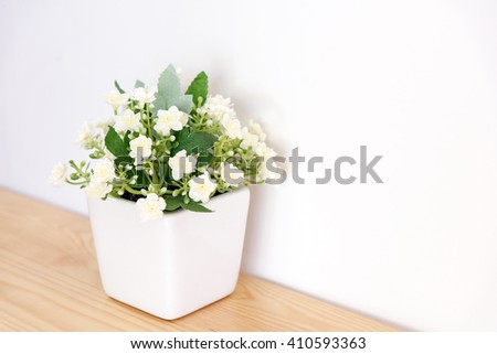 the artificial jasmine flower in the pot at the wooden table with the white wall background - stock photo