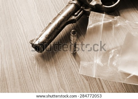 The artificial vintage plastic toy gun beside artificial bullet shape toy and plastic bag on sepia tone represent crime science investigation instrument concept related idea - stock photo