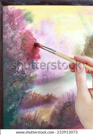 The artist paints a picture of the landscape using oily paints mounted on an easel. Selective focus on red brush - stock photo