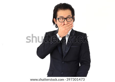 The Asian businessman closed a mouth with his hands. - stock photo