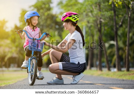 The asian family mother teaching children bicycle at the park - stock photo