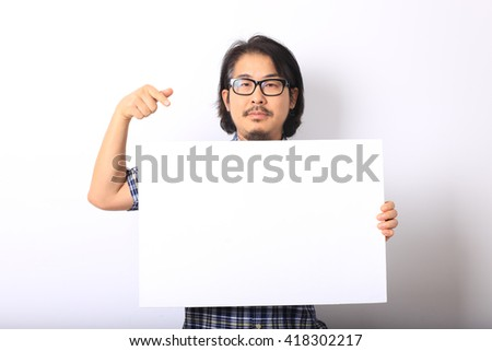 The asian man in the blue plaid shirt is pointing on white board. - stock photo