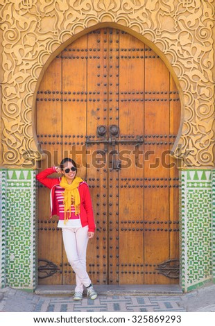 The asian woman tourist stand in front of the side gate of the Royal Palace in Fes, Morocco - stock photo