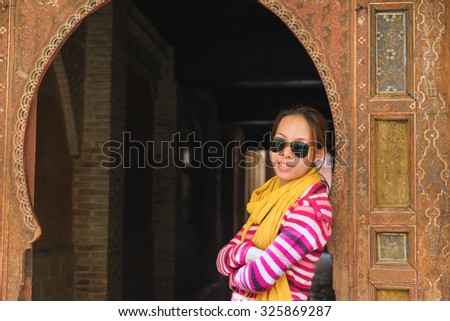The asian woman tourist stand in front of the wooden gate in Arabian style in Fes, Morocco - stock photo