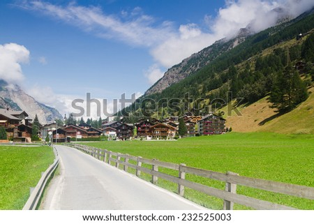 The asphalt road to a small village in the Swiss Alps. - stock photo