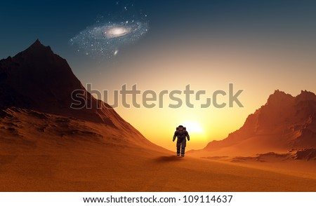 The astronaut  on the background of the planet. - stock photo