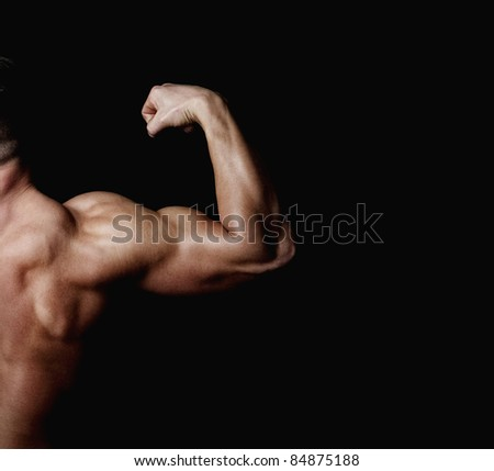 The athlete shows his powerfull arm and shoulder - stock photo