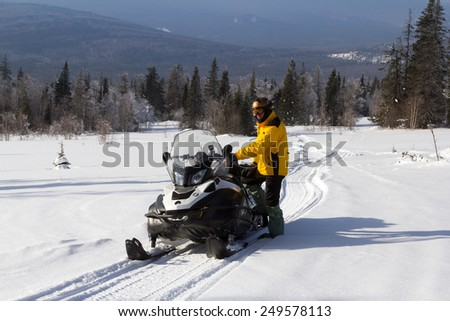The athlete stands near the snowmobile in the winter in the mountains of the Southern Urals. - stock photo