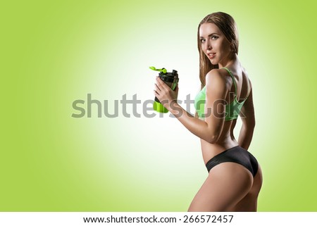 The athletic young beautiful woman with a protein cocktail in a shaker stands on a green background. Sports nutrition. - stock photo