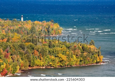 The Au Sable Light Station, surrounded by colorful fall foliage, stands on the Lake Superior shore of Michigan's Upper Peninsula at Pictured Rocks National Lakeshore near Grand Marais. - stock photo