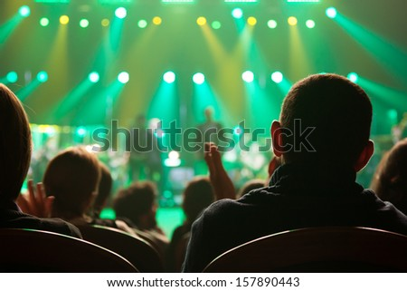 The audience applauded the artists on stage. - stock photo