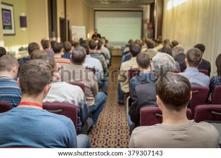 The audience listens to the acting in a conference hall. Pass through the center of the room between the rows toward the screen. - stock photo