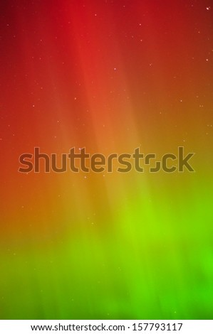 The aurora/northern lights shine in green, yellow and red over Lake Michigan. This is a close up of one of the curtains. - stock photo