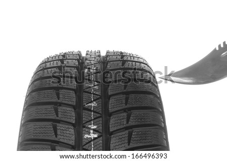 The automobile tire and knife isolated on white background - stock photo