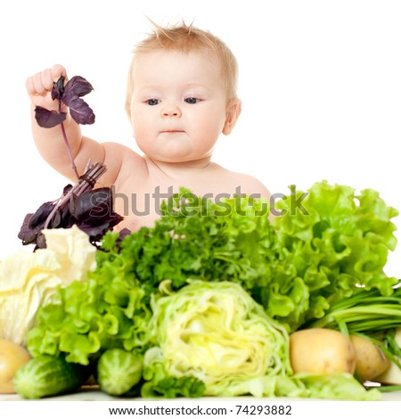 The babe in an environment of the fresh vegetables, isolated on the white - stock photo
